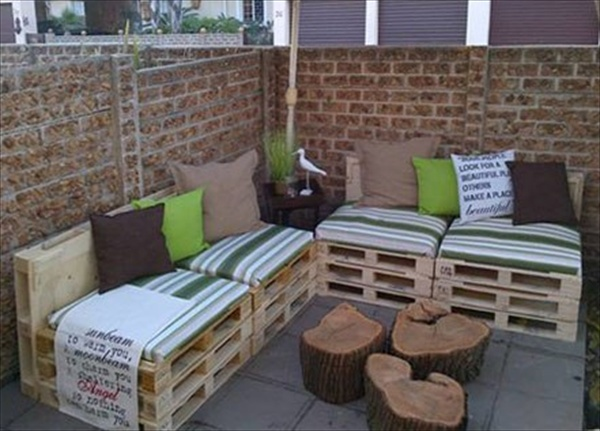 Charming-tree-trunk-coffee-table-with-wooden-pallet-couch-also-green-striped-pads-and-colorful-cushions-in-traditional-patio-design-with-bricks-wall